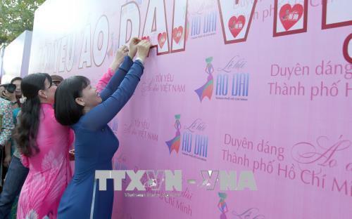 Các đại biểu tham gia dán decal trái tim thể hiện tình yêu áo dài Việt Nam. Ảnh: Quang Nhựt - TTXVN