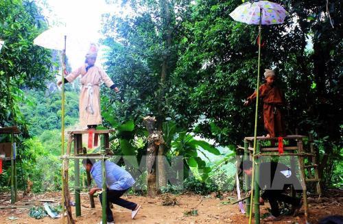 Các cậu bé đứng trên bồ đài trước khi rơi xuống để làm lễ. Ảnh: Phan Tuấn Anh - TTXVN